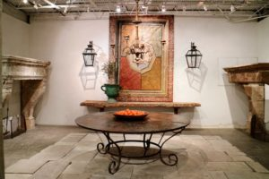 "The large antique iron table is from the courtyard veranda of a Maison Particulaire in Aix-en-Provence, France. Behind the table is a 16th century painted panel originally in a ""Salone delle Feste"" from a Palazzo in Mantona, Italy. It is flanked by a pair of 19th century wall lanterns."