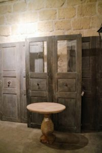 "In this room, a charming bespoke petite limestone table, and three pairs of 18th century Communication doors from a Maison de Maitre in Uzes, France. The wall is covered with creamy antique limestone ""bugets""."