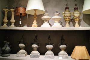 Here is a shelf filled with antique balustrades, candlesticks, stone elements, and other unique items electrified for use as lamps.