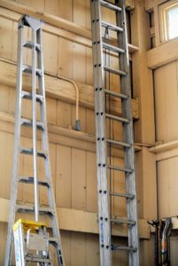 Ladders of various sizes rest against one wall above the wheelbarrows and close to one set of large barn doors.