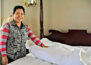 Here is my housekeeper, Sanu, stripping all the bedding, so she can put my new Lifekind Wooly Pillow Top in place.