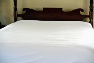 Next, Sanu places a deep pocket fitted sheet over the mattress pad, pillow tops and mattress. If you do not have deep pocket fitted sheets, use one fitted sheet over the mattress and a separate one over the toppers - both will help protect the surfaces.