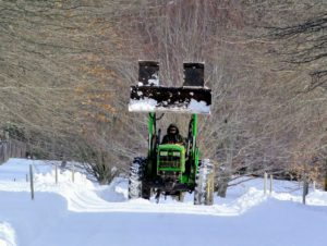 Here comes Chhiring on the tractor - ready to tackle more mounds of snow.