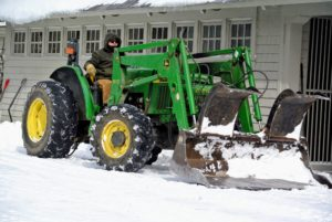 After the snow is blown and shoveled out of the way, the tractor is brought in to move big piles, so there is room to shovel more of the snow.
