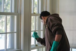 Carlos wipes the vinegar-water solution around entire window with a damp washcloth, making sure to get into the corners.