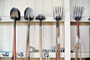 Tools are hung so that they are easy to find. Dirt is rinsed off outdoors before tools are put away.