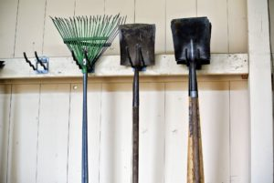 Here are the rakes and spades. Do you know the difference between a shovel and a spade? Shovels are broad-bottomed tools for moving loose materials, while spades tend to have a flat bottom edge for digging.