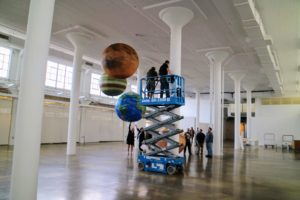 Our facilities crew used a scissor lift to hoist the giant planets to the ceiling.