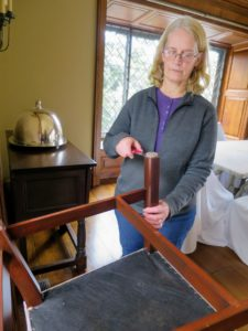 Here, Gretchen removes the old EZ Glide from the bottom of a dining room chair.