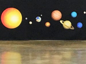 Fathead makes this solar system wall decal. We used a long roll of black paper to create the outer space. https://www.fathead.com/