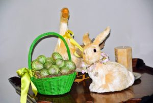 More ducks and stuffed bunnies next to a basket of blown out eggs adorn a nearby table.