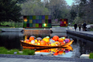 Float Boat sits in the Native Plant Garden. Koda Study #1 and Koda Study #2 are seen in the background. Chihuly's Koda Series displays the use of movement of color and light.