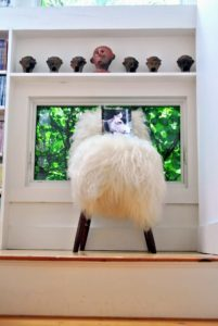 On the stairwell landing sits this faux fur covered stool with a photo of a cow on top.