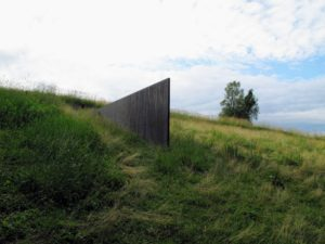 Richard Serra's 'Schunnemunk Fork', 1990–91. This installation was constructed on a 10-acre rolling field bordering woodlands. It consists of four weathering steel plates set lengthwise and inserted into the ground at designated intervals. Each plate is eight-feet high and two-and-a-half inches thick, with about a third of the length of each rectangular plate visible and the remainder buried in the earth.