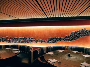 Drop-ceiling perimeter banquettes provide more intimate dining spaces for groups and families. The ceramic mural is by Pascale Girardin in collaboration with Rockwell Group - it provides a dramatic backdrop for the plush banquettes.