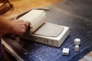 This shows an artisan pressing clay into a mold by hand. (Photo by Cybelle)