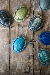 These paperweights recall the popular scarab, a beetle-like faience often used to represent immortality or rebirth. Pewabic in-house artisans, Technical Designer, Mario Lopez, and Fabrication Supervisor, Chris Mayse, collaborated on these for the Egyptian-inspired collection. (Photo by EE Berger)