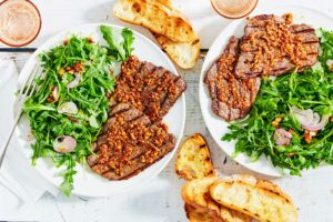 This is Minute Steaks & Grilled Bread with Smoky Almond-Paprika Butter. It's served with a smoky, savory compound butter flavored with smoked paprika, coriander, and smoked almonds. (Photo by Linda Pugliese)