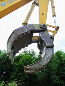 "The excavator is fixed with a large ""jaws grab"" attachment to pick up all the debris."