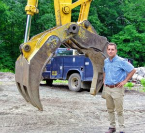 "Here is my new property director, Fred Jacobsen, standing next to the ""jaws grab"" to show just how large it is."