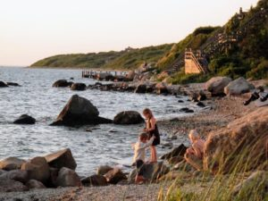 In the evening, we went to Montauk Beach. Here are Jude and Truman walking on the rocks, with their mother watching nearby.