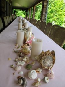 At first, we carefully spaced large conch shells and smaller shells along the length of the table, but realized this display took up too much room.