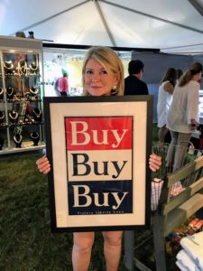 "Here I am with a great sign to ""Buy, Buy, Buy"" at the East Hampton Antiques Show. Kevin Sharkey captured this snapshot - see it on my Instagram @MarthaStewart48."