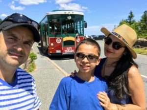 Rock and his family are on top of Cadillac Mountain. Oli's Trolley, a tour trolley, is parked right behind them.
