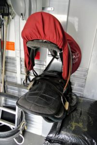 The saddles are loaded into the swing tack room of the trailer, which is located in a separate compartment in front of the stalls.