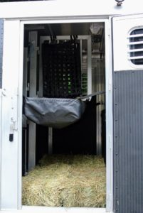 A feed bag designed especially for horse trailers will hold the hay at a reachable level, so the horses won't have to move too much in these close quarters.