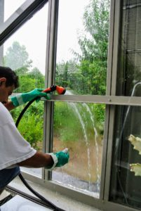 Next, Carlos rinses the window with plain hose water.