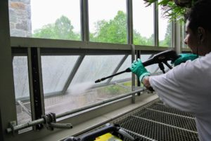 Here, Carlos uses a power washer to clean the debris off the screens. The lowest windows on this greenhouse automatically open when temperatures inside are too high. A lot of dust and debris can accumulate on these screens.