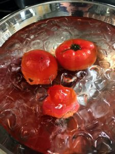The tomatoes cool in the ice as Enma removes the rest of the batch from the pot.