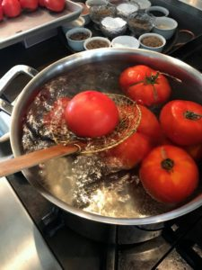 This only takes a a minute or two. Once they are soft, and the skins start to separate, using a slotted spoon, or spoon colander, remove the tomatoes from the boiling water.