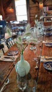 Each table is decorated simply with vintage and antique dishes and flatware. Grasses from the outdoor garden are placed in vases to serve as centerpieces.