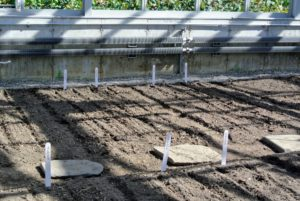Ryan places large wooden markers at the end of each bed, so they can be seen from the footpath. He also uses the bed preparation rake from Johnny's Selected Seeds to create furrows in the soil. http://www.johnnyseeds.com/