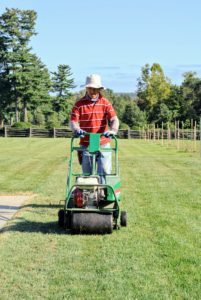 Dawa guides the aerator up and down the entire lawn, making sure he passes through every section of grass.