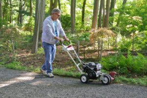 Fernando keeps both hands on the edger's handle at all times when it is running. Here he is guiding the machine slowly along the carriage road, keeping the blade tight against the paved surface, so it cuts through the earth. And always wear safety glasses to protect your eyes from flying debris.