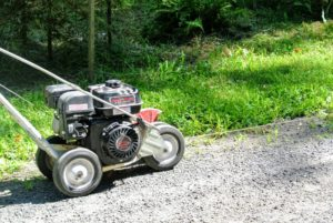 He lines up the twine where the edger should go, and then he lines up the edger, and continues to edge along the road.