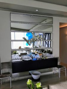 "Above Kevin's floating credenza decorated with blue and white straws and napkins is a metallic ""baby"" decoration on the mirror."
