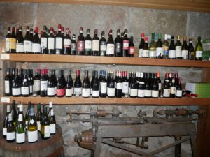 Wine bottles are stored on antique shelves.
