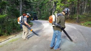 Rick and Mike follow closely and blow any extraneous pink gravel back into the center, where it can be collected on another pass.