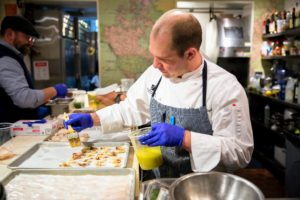 Meanwhile, in the kitchen, chefs are cooking and preparing their seafood appetizers. (Photo by Ester Segretto)