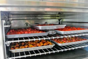 And here is another tip - if you need more oven space, place two oven safe Pyrex bowls upside down in the center of the two trays, so you can rest another tray of tomatoes on top.