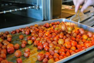 These tomatoes will roast for about four hours. Half way through, I checked on them and turned them on the tray.