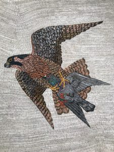 This is called 'Death From Above', 2017. It is a colored tile composite mosiac on wood panel measuring 72-inches by 72-inches. It depicts a falcon attacking a pigeon with taloned feet. The winter season is when hawks most aggressively prey on New York City's pigeons.