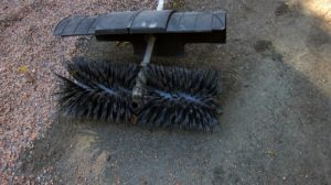 The attachment includes a large bristle brush and a protective shield, so debris doesn't fly up while in use. It helps get the caked in pink gravel pebbles off hard to reach areas of the carriage roads.