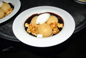 This is a salted caramel sundae with candied popcorn, peanuts, and chocolate fudge sauce.