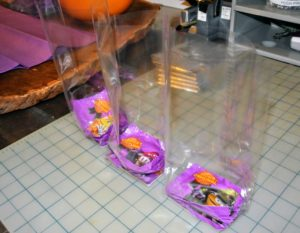 She places the M&M packets into the bottom of these cellophane bags. These bags are available online and can be so helpful for a lot of crafts.