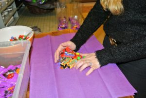 Shqipe places the loose candies and smaller wrapped chocolate bars in purple tissue paper - a fun Halloween color.